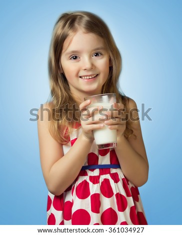 Child girl hold glass milk isolated on blue background. Kid female in red dress drinking,healthy lifestyle. - stock photo