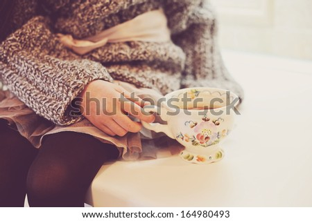 Child girl holding a vintage cup of hot drink, sepia tone added - stock photo