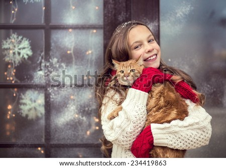 Child girl hugging her pet staying near her house decorated before Christmas - stock photo