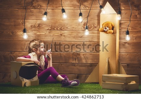 Child girl in an astronaut costume with toy rocket playing and dreaming of becoming a spacemen. - stock photo