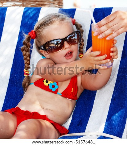 Child girl in glasses and red bikini drink orange juice. - stock photo