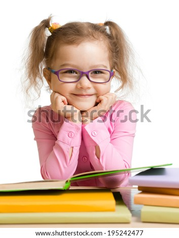 child girl in glasses reading book and smiling - stock photo