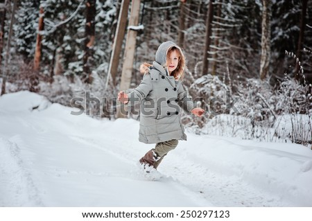 child girl in grey coat running in winter snowy forest - stock photo