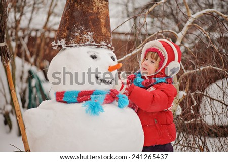child girl in red coat on ladder making snowman in winter garden - stock photo
