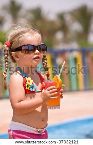 Child girl in sunglasses and red bikini drink orange juice. - stock photo