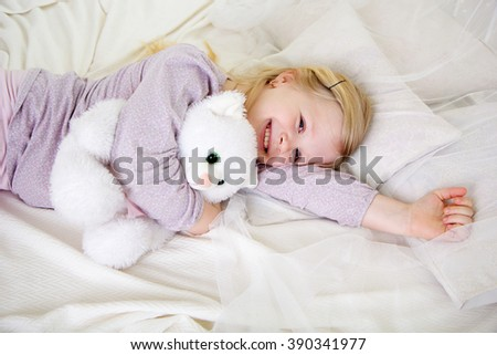Child girl in the bed with white teddy bear - stock photo