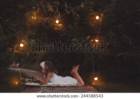 child girl in white dress reading book in warm summer evening garden with lights decoration - stock photo