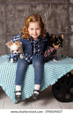 Child girl is holding two small chuhuahua dogs - stock photo