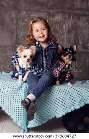 Child girl is sitting with chuhuahua dogs - stock photo
