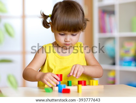 Child girl kid playing with sorter toys - stock photo