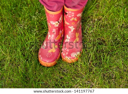 Child girl legs in pink galoshes on green grass background - stock photo