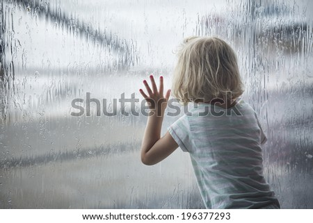 Child girl looking at raindrops on the window - stock photo