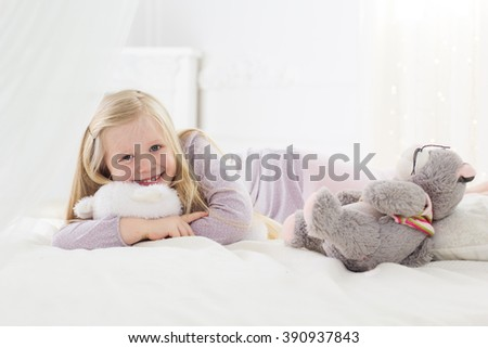 Child girl lying in bed with teddy bear - stock photo