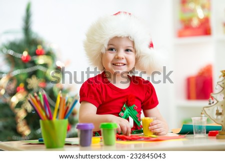 child girl making christmas tree of plasticine - stock photo