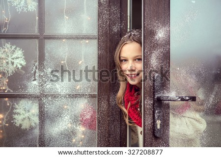 Child girl opens door and welcome guests, snow weather, house is decorated for Christmas - stock photo