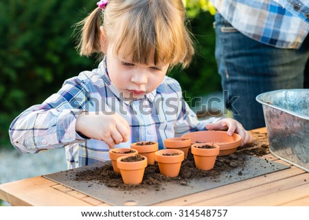 child girl planting flower seeds with mother. Gardening, planting concept - mother and daughter planting flower seeds  into small pots - stock photo