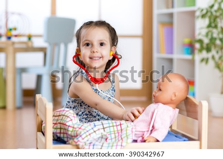 child girl playing doctor role game examining her doll using stethoscope sitting in playroom at home, school or kindergarten - stock photo