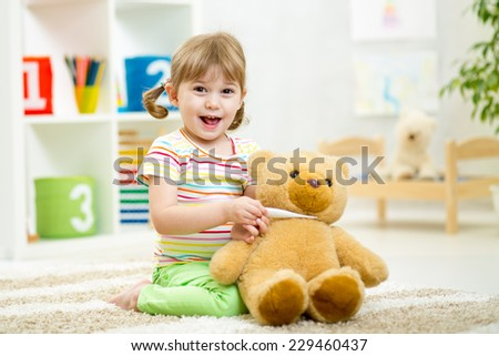 child girl playing doctor with plush toy at nursery - stock photo