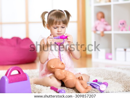 Child girl playing the doctor with her newborn baby doll in room - stock photo