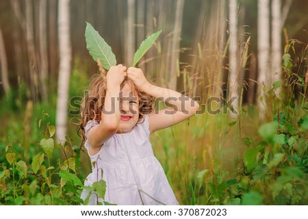child girl playing with leaves in summer forest with birch trees. Nature exploration with kids. Outdoor rural activities. - stock photo