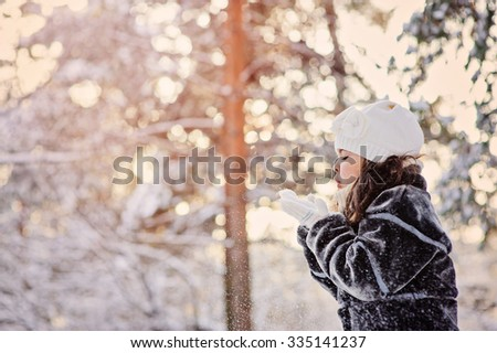 child girl playing with snow on winter forest walk. Cozy mood, seasonal outdoor activities. - stock photo
