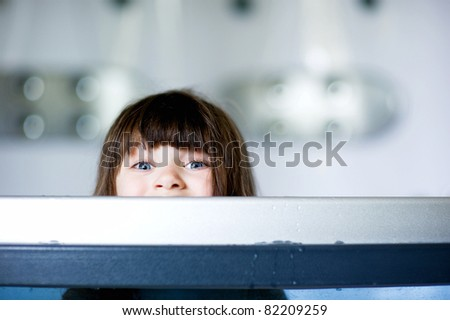 Child girl plays in a bathtub while looking out over a side - stock photo