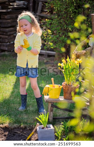 child girl plays little gardener and wearing rubber gloves in spring - stock photo