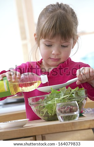 Child girl preparing sauce for green salad focus on oil flowing in the spoon - stock photo