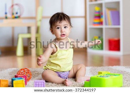 Child girl sitting among toys on carpet at home - stock photo