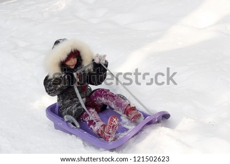 Child girl skate sled ride in the winter time - stock photo