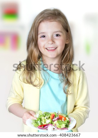 Child girl smiling face holding plate fresh salad.Kid eating vegetables.Healthy nutrition concept. - stock photo