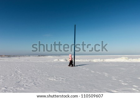 Child girl walks on snow near the sea - stock photo