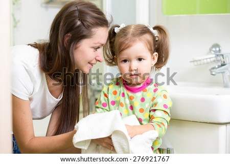 Child girl washing her hands in bathroom. Mom helps her little daughter. - stock photo