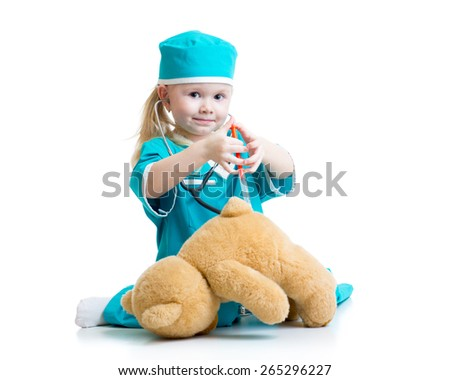 child girl with clothes of doctor playing plush toy - stock photo