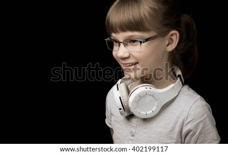 Child girl with headphones dancing at studio background - stock photo
