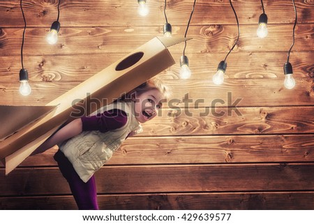 Child girl with toy rocket playing and dreaming of becoming a spacemen. - stock photo