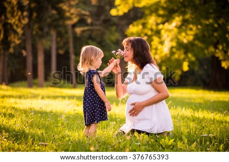 Child giving her her pregnant mother flower outdoor in sunny nature - stock photo
