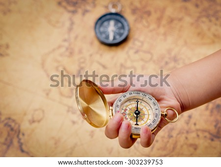 Child hand holding a compass on the map background. - stock photo