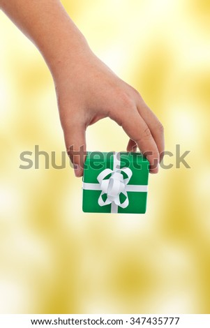 Child hand offering a gift - with copy space, on warm yellow background - stock photo