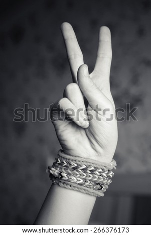 Child hand showing victory sign with rubber rainbow loom bracelets on wrist, trendy teenagers fashion accessories. Monochrome vintage retro tonal photo filter correction - stock photo