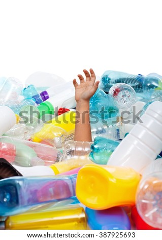 Child hand sticking out from plastic bottles garbage - environmental disaster concept, copyspace - stock photo