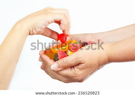 Child hand takes the candy from hands her mother closeup - stock photo