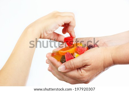 Child hand takes the jelly and sweets from hands her mother closeup - stock photo