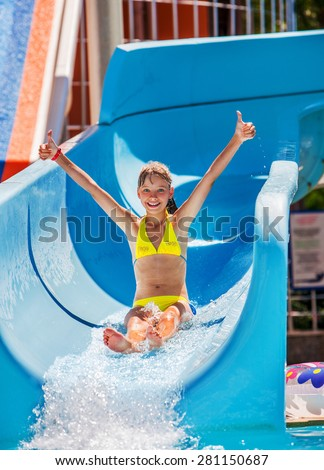 Child hand up on water slide at aquapark. Summer holiday. - stock photo