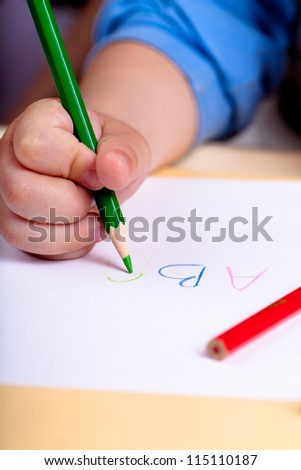 Child hand writing letters with green pencil - stock photo