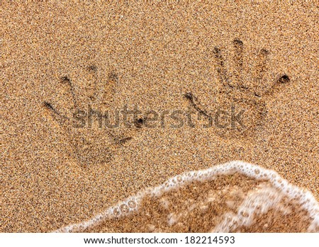 Child handprint on sand being washed away by sea wave - stock photo