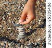 child hands building a rocks stack carefully - stock photo