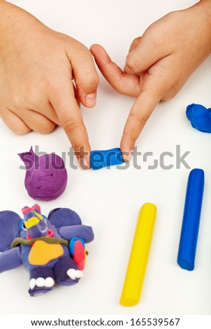 Child hands playing with colorful clay - closeup - stock photo