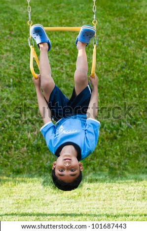 Child Hanging Upside Down on Monkey Bars in Playground - stock photo