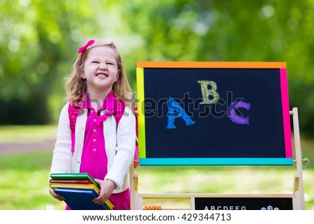 Child happy to be back to school. Funny little preschooler girl with backpack and books at black chalk board learning to write letters and read. Kids at preschool or kindergarten learn the alphabet. - stock photo